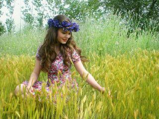 戴着花环蹲在小麦田里的美女人物