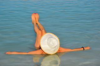 戴着草帽躺在水面上的女人