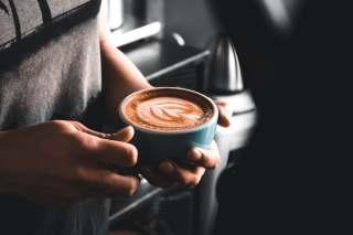 手端着一杯咖啡的图片