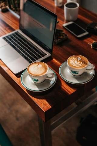 桌面上的笔记本电脑与两杯咖啡