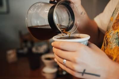 手拿咖啡壶倒咖啡的图片