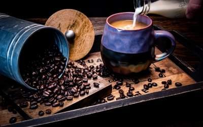 往杯子里到牛奶与咖啡豆图片