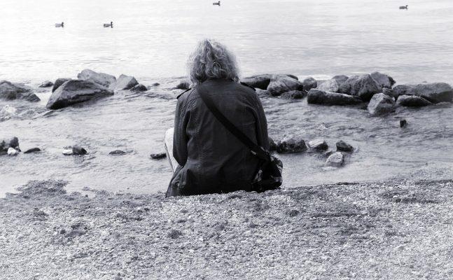 坐在海边的孤独人物背影