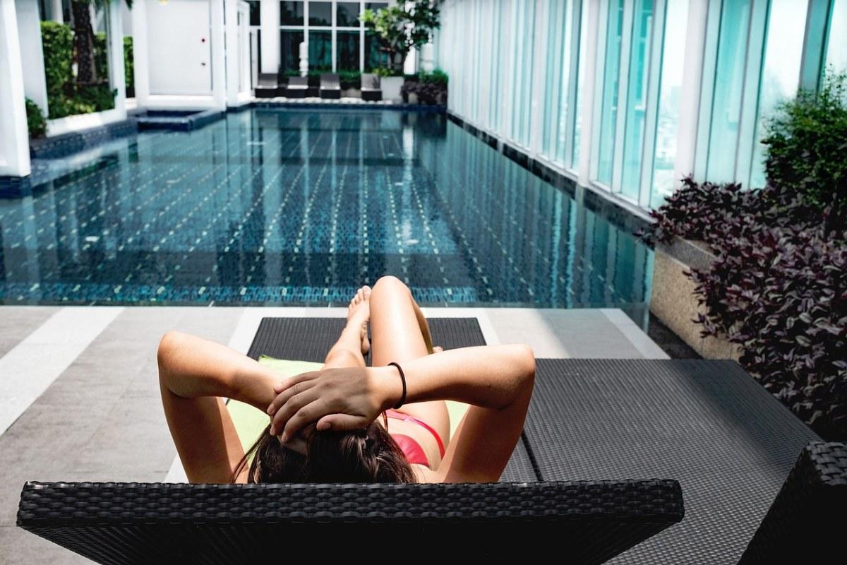 躺在游泳池边躺椅上的休闲女人