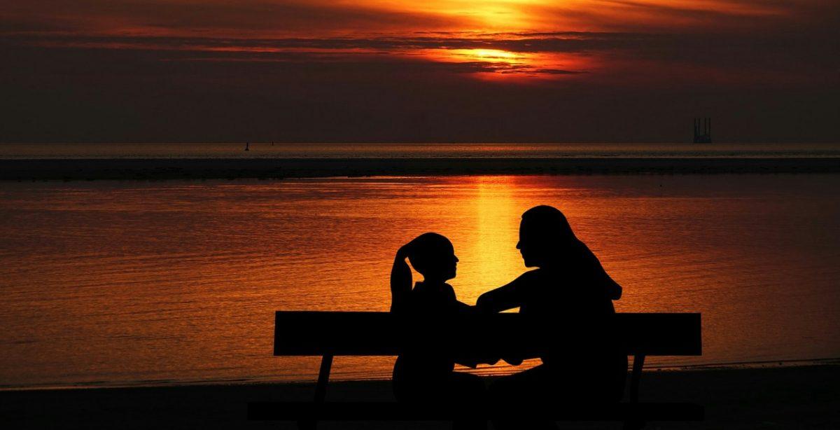 黄昏时作在长椅上的母女人物剪影