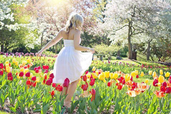 郁金香花丛中穿着白色连衣裙的美女背影
