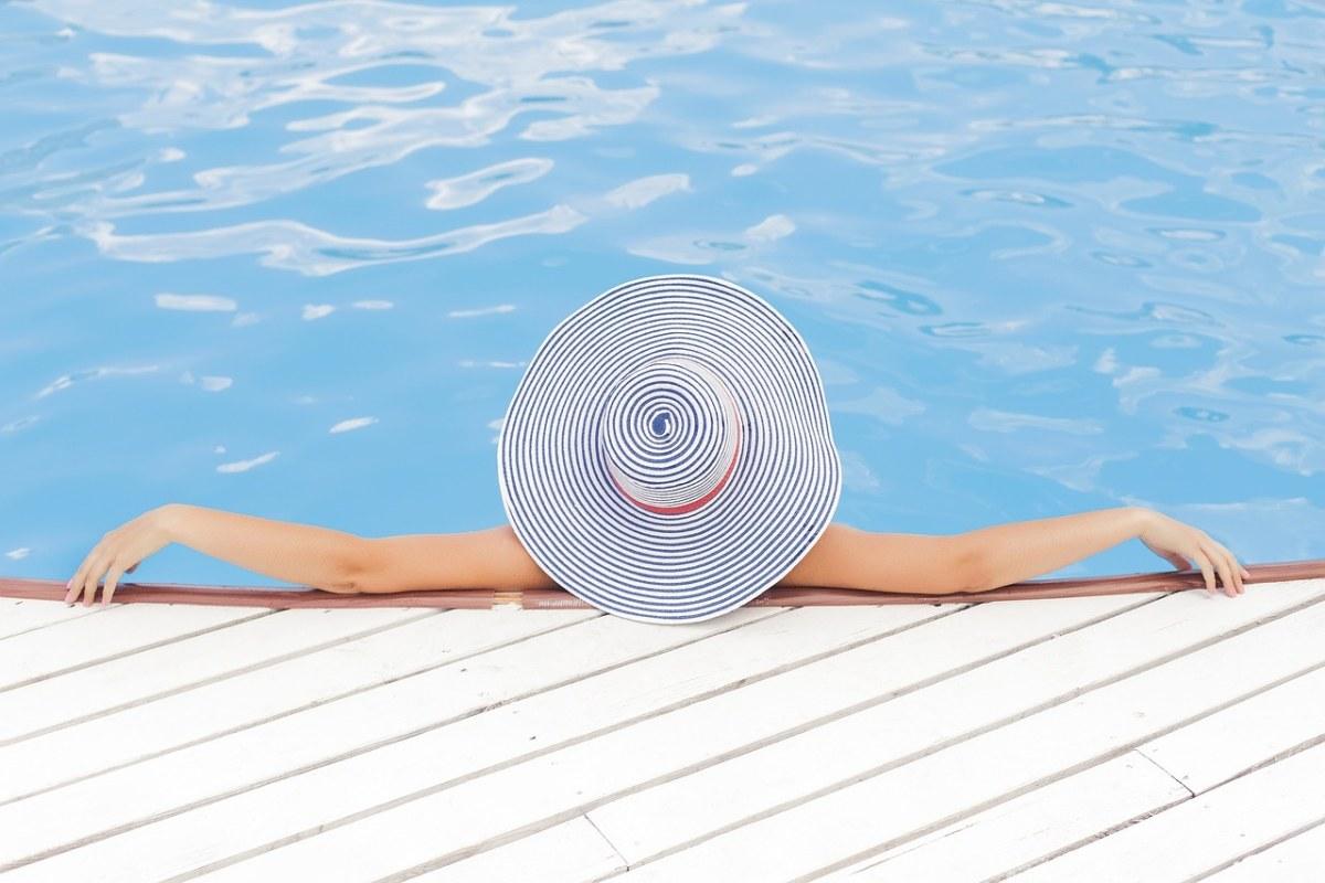游泳池带着草帽的女人